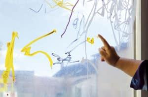 Enfant peint sur vitre avec son doigt
